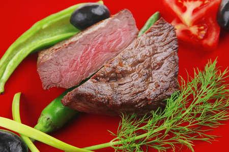 肉おいしい: グリル牛フィレ肉の唐辛子とトマトの白背景に分離された赤色のプレートで提供しています 写真素材