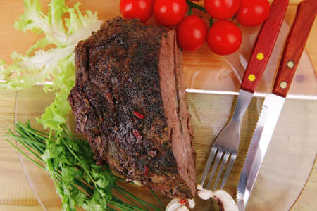 beef on transparent plate with vegetables over wood photo