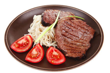 closeup of grilled steak with pasta and tomatoes on dark plate isolated over white background Stock fotó