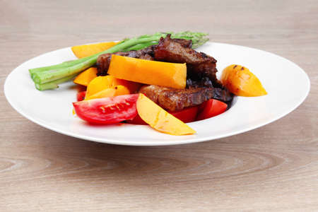 meat food : rare medium roast beef fillet with mango tomatoes and asparagus , served on white dish over wooden table Stock Photo - 11957826
