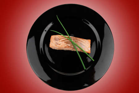 savory fish portion : norwegian salmon fillet roasted with green chinese onion, on black dish isolated over white background Stock Photo - 11957676