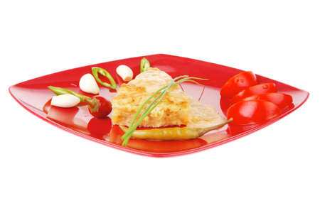 food : vegetable casserole piece over red plate ready to eat with chives tomatoes peppers and chives isolated over white photo