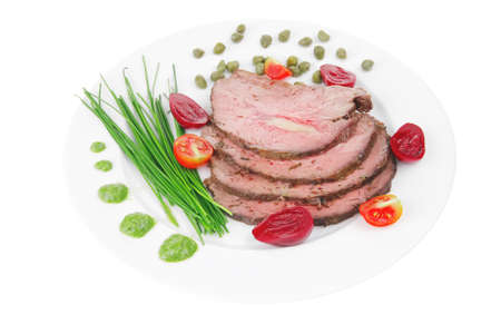 roasted meat served on white dish with capers photo