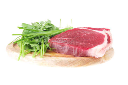 butchery : fresh raw beef lamb fillet ready to cooking with green stuff on wooden plate isolated over white background photo