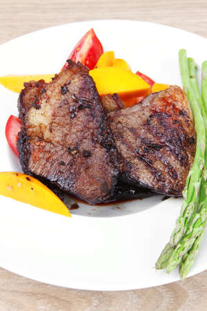 meat food : grilled red beef fillet with mango tomatoes and asparagus , served on white dish over wooden table Stock Photo - 11968141