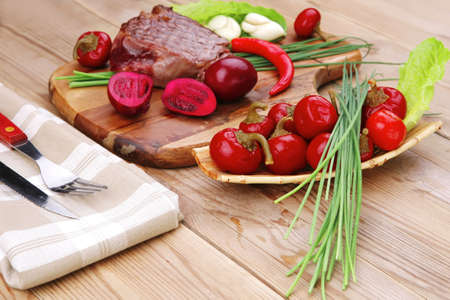 bbq : beef (pork) steak garnished with green staff and red chili hot pepper on wooden table with cutlery photo
