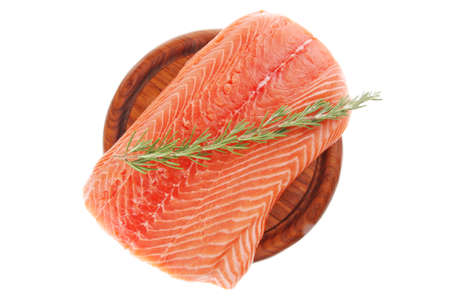 fresh raw red fish fillet on wooden plate and rosemary photo