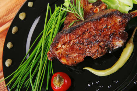 cooked pepper ball: image of served meat: spiced barbecued ribs on black plate with peppers chives and capers