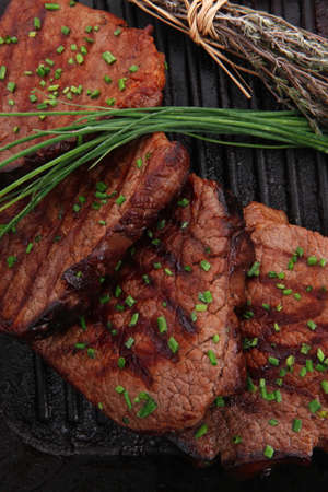 roasted beef meat fillet on bbq pan with cayenne pepper isolated on white background photo