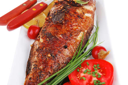 savory isolated on white: whole fried sunfish over plate with tomatoes lemons and peppers photo