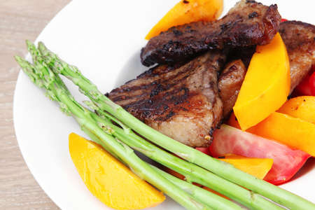 meat food : rare medium roast beef fillet with mango tomatoes and asparagus , served on white dish over wooden table Stock Photo - 12000697