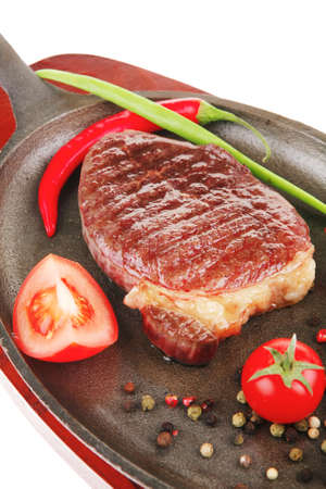 meat entree : grilled beef steak served with hot cayenne peppers red tomato green chives on metal pan isolated over white background photo