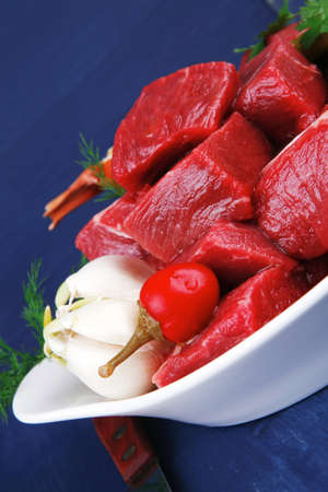 raw fresh beef meat slices in a white bowls with onion and red peppers serving on blue table with cutlery photo