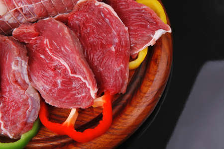 fresh raw meat on wooden board with slices photo
