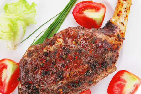 roast meat shoulder on white with tomatoes chives and green lettuce isolated on white background photo