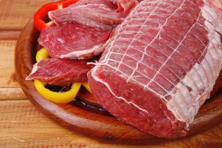 red meat on wooden table ready to cook photo