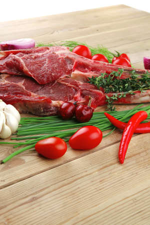 raw meat : boned fresh lamb ribs served with thyme , red chili pepper , cherry tomato , and green onion over wooden table Stock Photo - 12078186