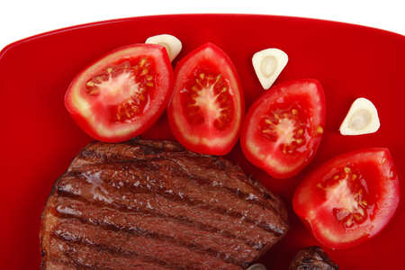 italian cuisine : grilled steak with pasta and tomatoes on red plate isolated over white background Stock Photo - 12078229