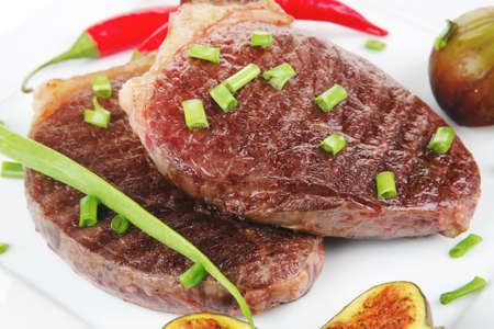 meat entree : grilled beef steak served with red hot cayenne peppers green chives and sweet figs on plate isolated over white background photo