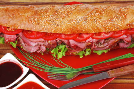 french sandwich on red plate : long baguette with smoked chicken sausage with sauces over wood photo