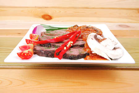 grilled beef slice on plate over wooden table photo
