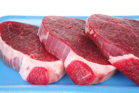 uncooked meat : raw fresh beef pork tenderloin strip ready to cooking on blue tray isolated over white background photo