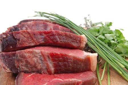 bloody raw beef meat on wooden plate with chives and thyme isolated on white background photo