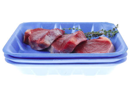 fresh raw beef fillet medallions with thyme twig on blue tray isolated over white background photo