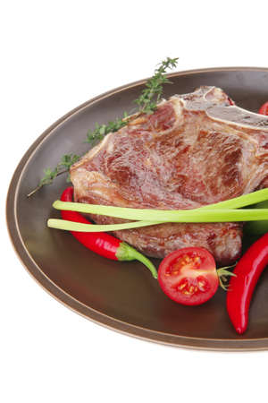 meat food : grilled beef spare rib on dark dish with thyme pepper and tomato isolated over white background photo