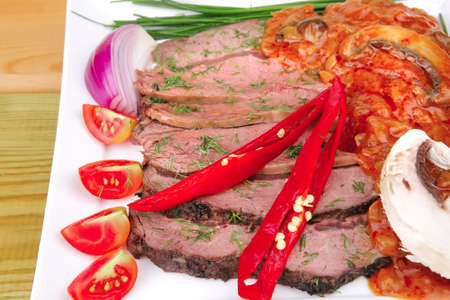 beef slice on white plate with peppers wooden table photo