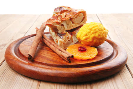 sweet apple cake on wooden table with lemon and cinnamon sticks photo