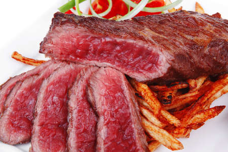 meat and potato : rare grilled beef steak served with pepper and tomato over plate isolated on white background photo