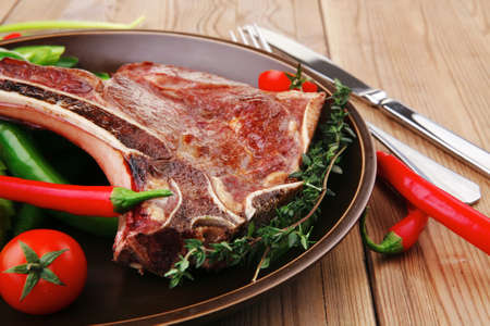savory : roasted beef spare rib on dark dish with cutlery thyme pepper and tomato on wooden table photo