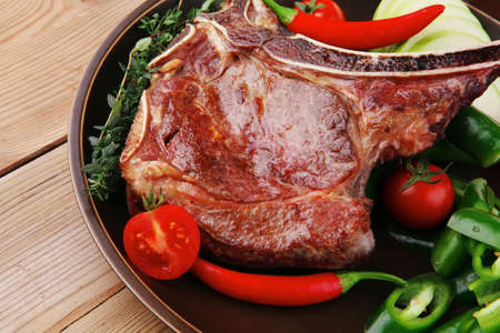 meat food : roast rib on dark dish with thyme pepper and tomato on wooden table photo