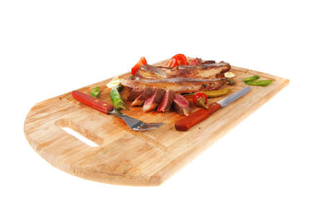 fresh roasted lamb meat fillet ready on wooden board with tomatoes and red pepper isolated  over white background photo