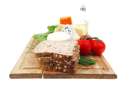 delicatessen cheeses on wooden board with vegetables olive oil and bread isolated over white background photo