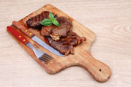 barbecued beef fillet on wooden plate with cutlery over table photo