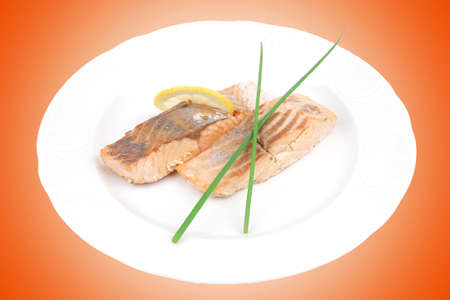 sea food: sea food : roasted pink salmon fillet with chinese onion, and lemon on white dish isolated over white background