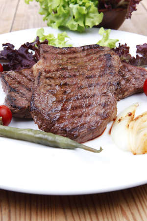 frame less: meat food : two grilled steak on green lettuce salad , with roast onion and red hot chili peppers , on dish over wooden table Stock Photo
