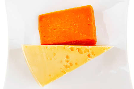 cheese : french gourmet triangles of yellow parmesan and orange cheddar on a plate isolated over white background Stock Photo - 12268990