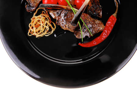 roast ribs on plate with tomatoes and chives photo