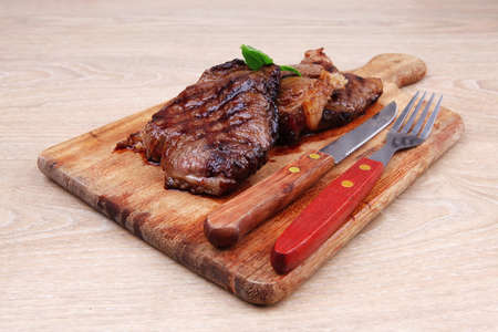 barbecued beef fillet on wooden plate with cutlery over table Stock Photo