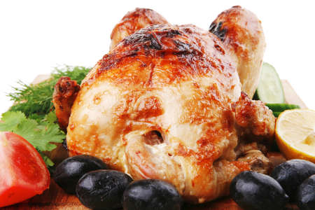 poultry : fresh grilled whole chicken with black olives and raw tomatoes on wooden board isolated over white background photo