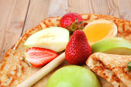 sweet food : big thin pancake with honey strawberries and apple on wooden table Stock Photo - 12528640
