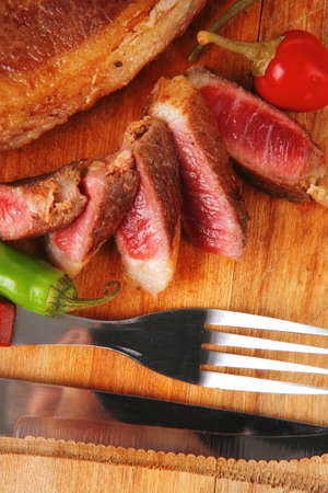 red meat steak sliced on wooden board with green hot pepper and cutlery isolated  over white background photo