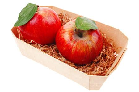 over packed: roja fresca manzana madura gemelos embalan con la caja de madera aislada sobre fondo blanco Foto de archivo