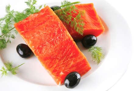 sinlge pink salmon bit on a big white dish photo
