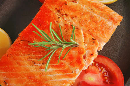 food: hot baked salmon piece served on iron pan over wooden plate isolated on white background photo