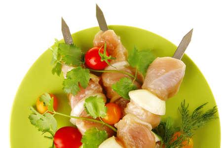 served raw chicken kebabs on dark plate photo