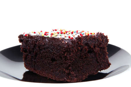 sweet dessert : chocolate cake coated with chocolate on black saucer isolated over white background photo